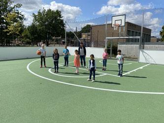 Bei bestem Wetter erkundet die Schulleiterin Frau Hagemeier mit Kindern aus den Klassen 1 und 4 das neue Fußballfeld.
