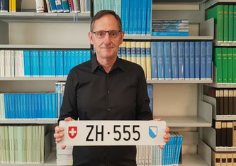 Mario Fehr hält das Kontrollschild «ZH 555» in den Händen, das bald unter den Hammer kommt.