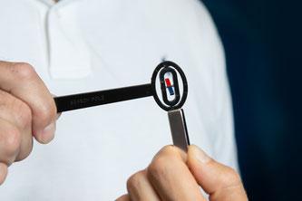 Das Gerät zur Bestimmung der Ausrichtung des Magnetfeldes funktioniert wie ein Kompass. Hält man es an einen Magneten (hier grau-silber), dann dreht sich der blau-rote Stift so, dass sein rotes Ende in Richtung des Nordpols zeigt. (Foto: PSI)
