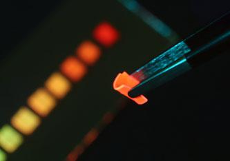 Der neu entwickelte Solarkollektor bei Bestrahlung mit blauem LED-Licht: Das Polymer-Material ist so flexibel, dass es sich mit einer Pinzette biegen lässt. Bild: Empa