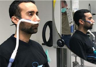 Eine gesunde männliche Testperson sitzt vor dem Schlierenspiegel und trägt das NHF-Therapiegerät. Amayu Wakoya Gena Bauhaus-Universität Weimar