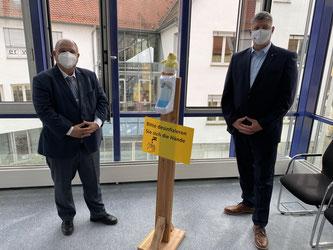 """Bürgermeister Scholz (links im Bild) und Roland Zitzmann mit freundlichen Hinweis zur Einhaltung der """"AHA-Regel"""": Abstand halten – Hygieneregeln beachten – Atemmaske und:  wenn möglich bitte so gut lüften wie im Sitzungssaal des Sersheimer Rathauses"""