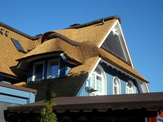 Giebeldetail einer Villa mit Reetdach und blauer Fassade