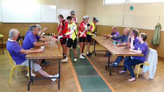 Control marshals stamping the control cards of randonneur cyclists at Paris-Brest-Paris 2015 Randonneur