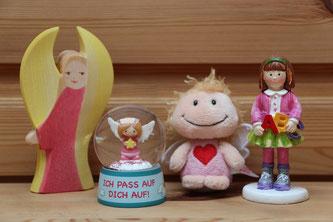 Ein Holzengel von Ostheimer, eine kleine Schutzengel-Schneekugel, ein Schutzengel-Schlüsselanhänger und eine Schulkind-Figur