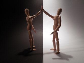 Zwei Holzfiguren schlagen ein