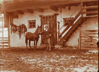 Dieses Bild zeigt den Urgroßvater von Martin Danklmaier – Florian Danklmaier –  mit einem Roß vor der Stalltüre