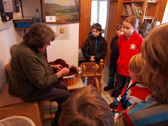 Zunächst muss aus der Wolle ein Faden gesponnen werden. Die NAJUs schauen gespannt zu ... - Foto: Kathy Büscher