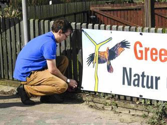 Dr. Nick Büscher befestigt das Banner am Zaun. - Foto: Kathy Büscher
