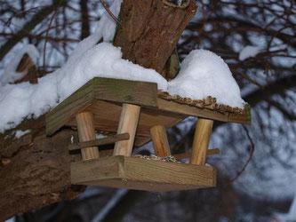 Im Baum aufgehängtes Futterhaus, das Futter ist vor Feuchtigkeit geschützt. - Foto: Kathy Büscher