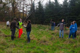Die ehrenamtlichen Naturschützer mit den neuen Bäumen auf der Erweiterungsfläche. - Foto: Kathy Büscher