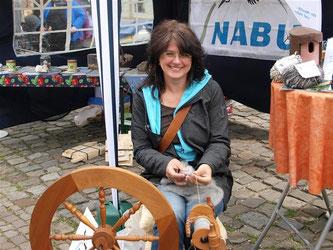 Britta Raabe am Spinnrad auf dem Kirchplatz. - Foto: Kathy Büscher