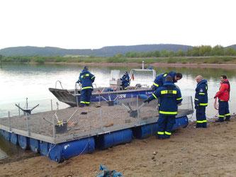 Mit Booten zieht das THW die Flöße aufs Wasser. - Foto: Britta Raabe