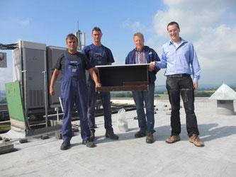 H. Erxleben, M. Godenrath, P. Ernst von der Firma O-I-Glasspack mit Nick Büscher auf dem Dach der Firma. - Foto: NABU