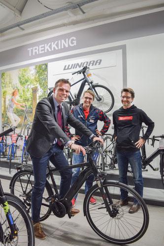 Bürgermeister Oliver Schulze (vorne) drehte gleich noch eine Probefahrt mit dem neuen Gemeinde E-Bike. Im Hintergrund zu sehen sind Ulrich Fenn (Marktleiter Schauer; von li) und Dominik Thiele (Regional Director D-A-CH).