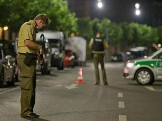 Ein Polizist mit Maschinenpistole bewacht in Ansbach die Zufahrtsstraße zur Altstadt. Foto: Daniel Karmann
