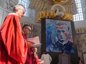 Ein riesiges Gemälde mit einem Porträt von Pater Engelmar Unzeitig wird enthüllt. Foto: Nicolas Armer