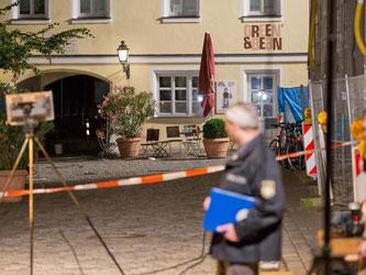Ein Polizist betrachtet den Tatort in Ansbach. Foto: Daniel Karmann