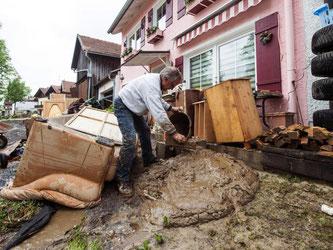Ein Helfer kippt in Triftern einen Eimer mit Schlamm vom Hochwasser vor ein Haus. Foto: Armin Weigel