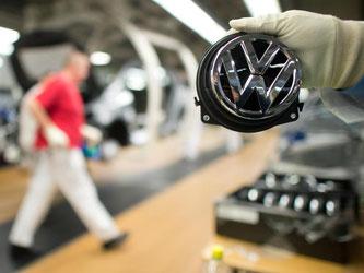 Ein Mitarbeiter zeigt in Wolfsburg ein Volkswagen-Logo. Foto: Foto: Julian Stratenschulte