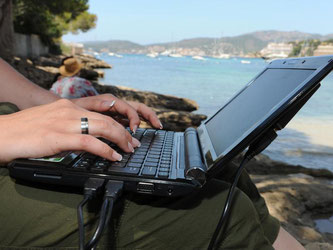 Eine Frau arbeitet am Strand von Santa Poca auf Mallorca mit ihrem Laptop am Wasser. Foto: Patrick Seeger