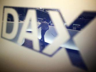 In der Börse in Frankfurt am Main spiegelt sich ein Händler in einem Logo des Deutschen Aktienindex (DAX). Foto: Fredrik von Erichsen