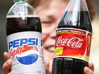 Eine Frau hält eine Flasche Pepsi und eine Flasche Coca-Cola. Foto: Maurizio Gambarini/Archiv