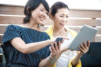 スマートフォンとタブレットを操作する女性たち