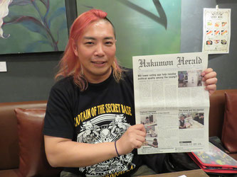 Shimizu poses with a copy of Hakomon Herald in hands.