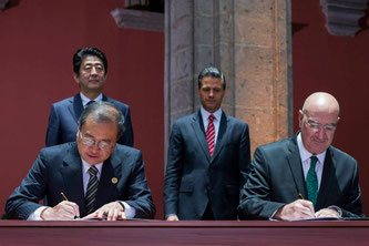 Shuichiro Megata (front left), then Japanese Ambassador to Mexico, signs a document in Mexico City in July 2014, witnessed by Japanese Prime Minister Shinzo Abe (back left) and Mexican President Enrique Peña Nieto (center).