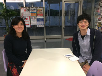 Yoshida (right) interviews Akiyama (left) at the second floor, 11th building in front of the International Center .