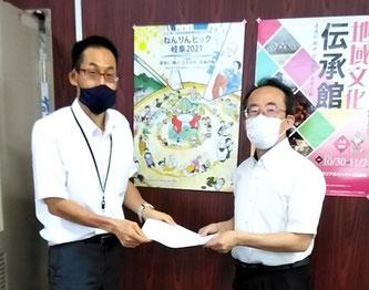 ねんりんぴっく推進事務局の今井事務局長に要請書を手渡す長谷川委員長(右)