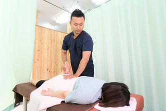 クライアントにマッサージ・ストレッチをして姿勢を整える鍼灸師