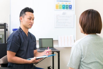 腰痛クライアントと問診する鍼灸師