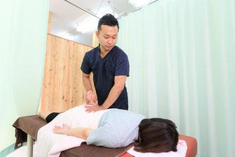 腰痛患者にマッサージ・ストレッチをして姿勢を整える鍼灸師