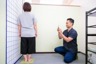 腰痛クライアントの姿勢をチェックする鍼灸師