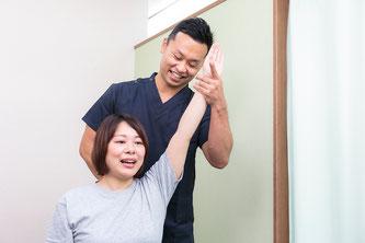 腰痛クライアントの筋肉・関節・神経をチェックする鍼灸師