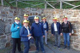 Das Bild zeigt 6 Teilnehmer an der Besichtigung des Besucherbergwerks mit dem Führer am Eingang des Bergwerks.