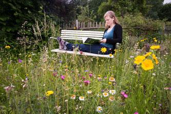 Eine Frau sitzt auf einer Bank mit einem Buch, im Vordergrund eine blühende Wiese