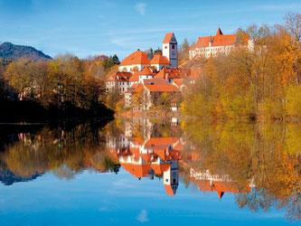 Blick über den Lech auf Füssen im Herbst - im Hintergrund sieht man unter anderem das Kloster St. Mang. Foto: Füssen Tourismus/Peter Samer