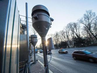 Autos fahren an einer Feinstaubmessstation in Stuttgart vorbei. Foto: Lino Mirgeler/Archiv