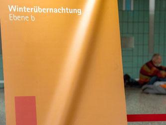 """Ein Banner """"Winterübernachtung Ebene b"""" weist in Frankfurt am Main auf Übernachtungsplätze im Bahnhof hin. Foto: Andreas Arnold"""