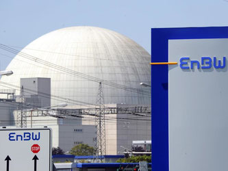 Hinter einem EnBW-Logo ist das Kernkraftwerk Philippsburg zu sehen. Foto: Uli Deck/Archiv