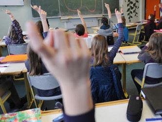 Schüler heben in einem Unterrichtsraum ihre Finger. Foto: Franziska Kraufmann/Archiv