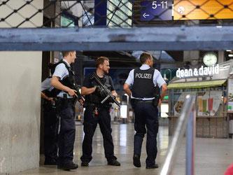 Polizisten mit Maschinenpistolen stehen in München am Hauptbahnhof und sichern das Gelände. Foto: Andreas Gebert
