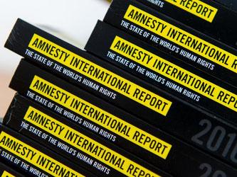 Ausgaben des Jahresberichts 2016/2017 von Amnesty International liegen in Berlin auf einem Tisch. Foto: Monika Skolimowska