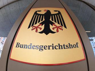 Ein Hinweisschild mit Bundesadler am Bundesgerichtshof (BGH). Foto: Uli Deck/Archiv