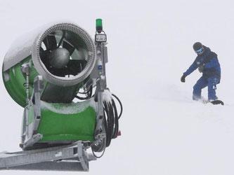 Ein Snowboardfahrer fährt auf dem Feldberg an einer Schneekanone vorbei. Foto: Patrick Seeger/Archiv