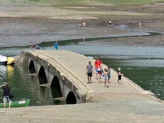 Touristen gehen über eine vierbogige Brücke. Sie ist mehr als 100 Jahre alt und nur bei Niedrigwasser tritt sie zu Tage. Foto: Uwe Zucchi
