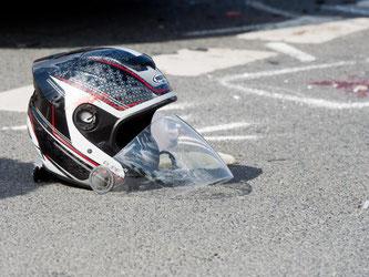 Ein Motorradhelm liegt nach einem schweren Verkehrsunfall auf der Straße. Foto: Julian Stratenschulte/Archiv/Symbol